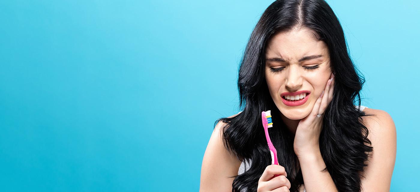 Mujer con dolor de diente durante el cepillado bucal