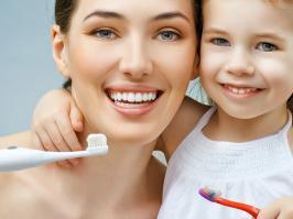mamá e hija lavándose sus dientes