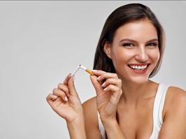 Mujer con implantes dentales rompiendo un tabaco