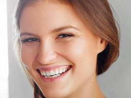 Mujer sonríe después de recuperarse de Halitosis