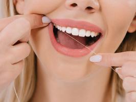 mujer usa hilo dental