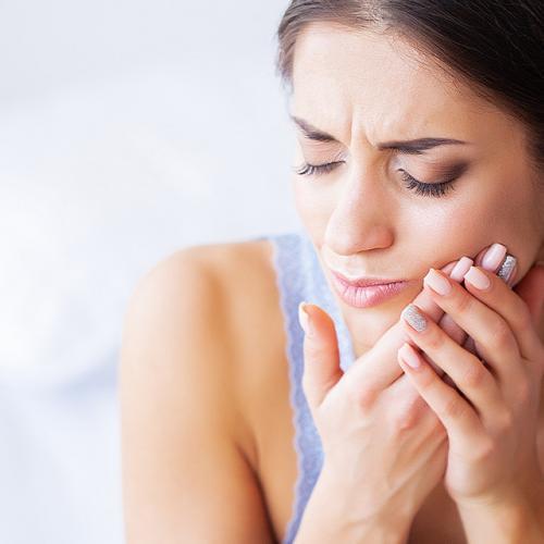 mujer con dolor de diente por infección dental